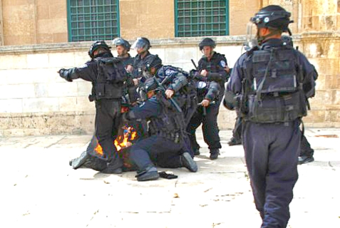 An Israeli soldier who got hit by a Molotov cocktail is seen on fire during a protest after Friday prayers outside the Temple Mount compound on March 8, 2013.