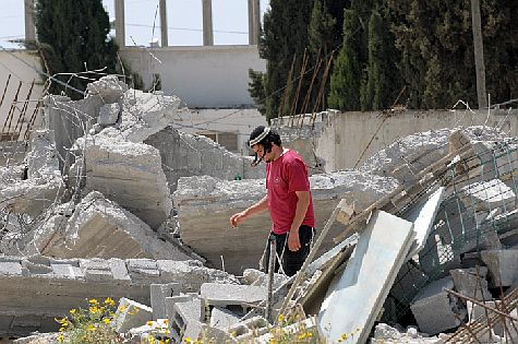 A Jewish settlers picks through the ruins of his demolished house in Shavei Shomron in 2010. (archive)