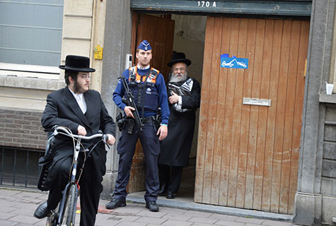 Police stand guard at Jewish school in Brussels following attack that left four dead in 2014.