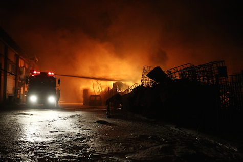 Fire crews battle blaze started when Hamas rocket hit factory in Sderot, June 28, 2014