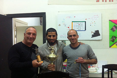 Yuval (center) with coach Ami and Shai holding trophies and a medal won by the soccer team.