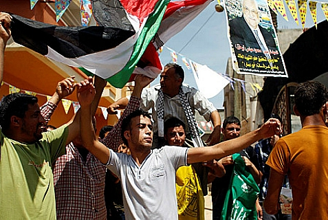 Palestinian protesters wave the flags of Palestinian political movements, Fatah (yellow) and Hamas (green) as they chant slogans in support of the national reconciliation and the announcement of the formation of a national unity government between the two factions, in Khan Yunis, in the southern Gaza Strip, on May 29, 2014.