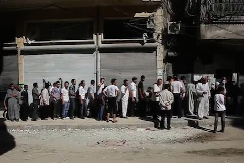 Aleppians waiting in a bread line during the Syrian civil war.