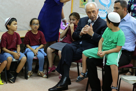 Consistent morals, even in the face of rocket fire: then-President Shimon Peres visits a Sderot summer day camp. (archive)
