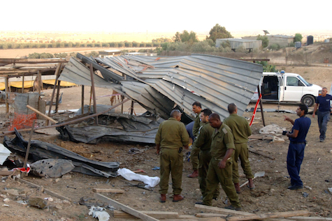 IDF officers examine the remains of a shed in Beer Sheva that was hit by a Grad rocket, July 14, 2014.