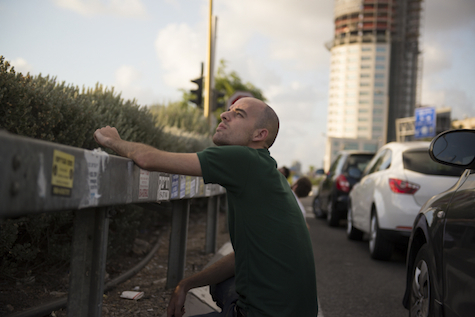Israeli man tries for glimpse of Iron Dome rocket interception, July 15, 2014.