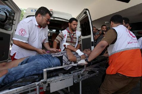 Medics wheel a wounded Palestinian Arab into the emergency room of Shifa hospital in Gaza City, northern Gaza.