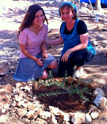 Ruth Lieberman and her daughter, Merav, plant a tree in Eyal Yifrach's memory at the new site created to honor the boys, Givat Oz v'Gaon.