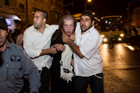 Undercover police officers arrest a Haredi demonstrator during a protest at the Bar Ilan intersection in Jerusalem Sunday.