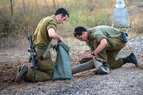 IDF soldiers examine fragments from a rocket that landed near Kibbutz El Rom, fired from Syria on July 14, 2014.