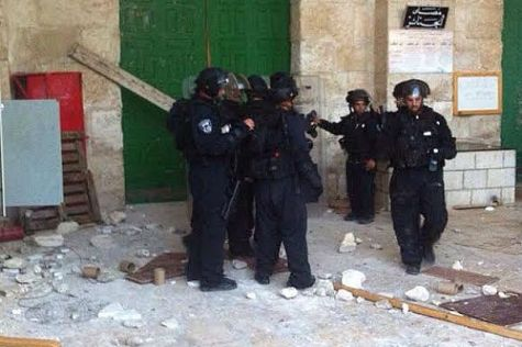 Police stand amid pile of rocks after shutting doors to Al Aqsa mosque.