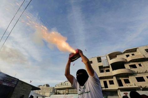 Arab youth shoot fireworks during clashes with Border Police in Shuafat in Jerusalem.
