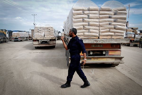A Hamas policeman walks past trucks loaded with cement which entered the Gaza Strip from Israel through the Kerem Shalom crossing.