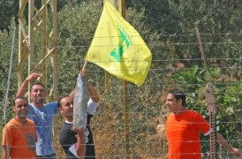 A Lebanese man holding an Israeli mortar shell and a Hezbollah flag along the Israel-Lebanon border opposite Metulla. (archive 2006)