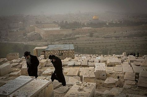 Haredim brave high winds at Har Zeitim (Mount of Olives) cemetery in Jerusalem.