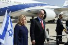 Prime Minister Netanyahu speaks to reporters with his wife at his side at Ben Gurion Airport Sunday morning.