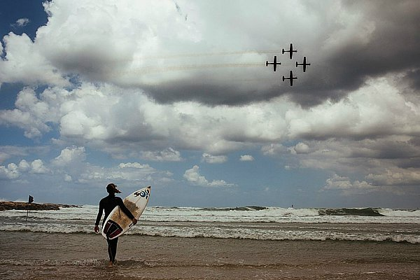 Surfer braves the cold, wind and rain as Israel Air Force jets fly over the Tel Aviv beaches.
