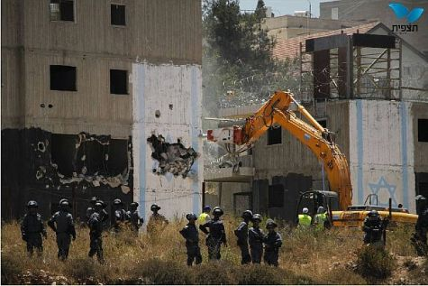 First, the demolition crew tore out the heart of the Israeli flag on the building.