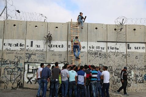 Palestinian Authority Arabs climb a section of Israel's separation barrier in the village of Al-Ram, as they try to avoid crossing Israeli-controlled checkpoints to reach the al-Aqsa mosque compound at the Temple Mount in Jerusalem's Old City to attend Friday prayers in the fasting month of Ramadan.