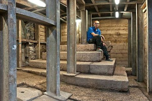 Dr. Joe Uziel, codirector of the excavation from the Israel Antiquities Authority, sitting atop the stepped structure from the Second Temple period.