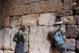 A man and a women praying together at the Little Western Wall, bothered by no one.