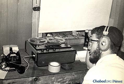 "In January 1970, for the very first time, the Rebbe's talk at the farbrengen after Shabbat was broadcast live through a phone-line hook-up to 1,000 Chassidim gathered in the village of Kfar Chabad, Israel. Inside the ""World Lubavitch Communications Center"" (WLCC), Meni Wolff can be seen working on the broadcast. (Photo: Mulik Rivkin Archive)"