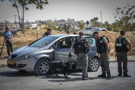Israeli Border Guard Police officers check drivers on their way out of the Jerusalem Arab neighborhood of Jabel Mukabar.