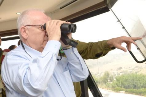 Israeli president Reuven Rivlin looking through binoculars during his visit in the Northern district border of Israel