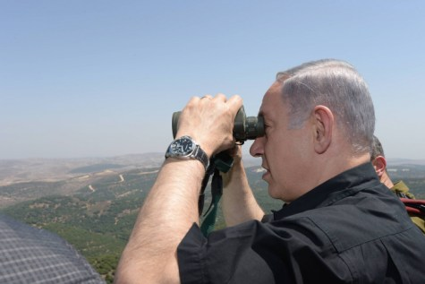 Israeli Prime Minister Benjamin Netanyahu looks through binoculars during his visit in the Northern district border of Israel.