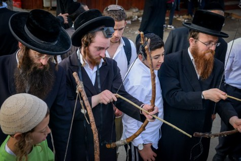 Jewish men shooting a bow and arrow in Meron on Lag B'omer