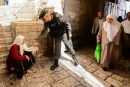 An Israeli Border Police officer gives money to a Muslim Arab woman during the second Friday prayers of the holy Islamic month of Ramadan in the Old City of Jerusalem, June 17, 2016.