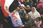 Opposition protesters shout slogans and show a defaced poster of their president.