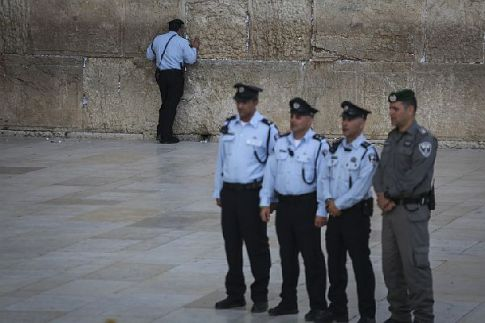 An Israeli police officer prays at the Western Wall as a group of other officers pose for a picture, before a Memorial Day ceremony held at Judaism's holiest site, in Jerusalem's Old City, May 10, 2016.