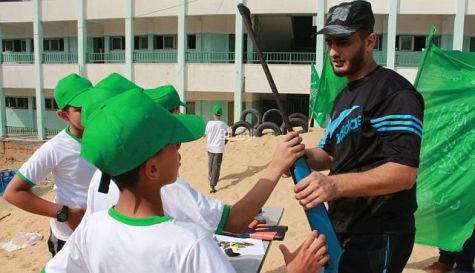 Hamas 'camp counselor' hands a gun to a child in Gaza.