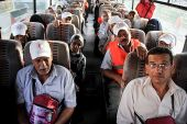 Palestinian Authority residents wave as they sit in a bus before leaving the Rafah border crossing for the annual hajj pilgrimage in Mecca from southern Gaza on September 7, 2015.