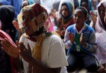 Mulheres cristãs da Etiópia e da Eritreia louvam em igreja improvisada no campo de refugiados, na França. (Foto: Reuters)