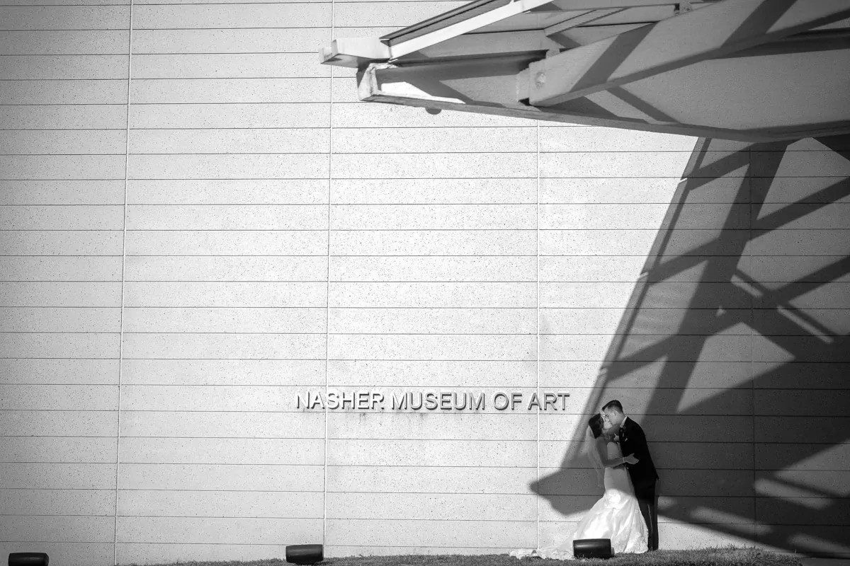 Wedding portrait of newlyweds outside Nasher Museum in Durham, NC incorporating shadows from the structure's architecture