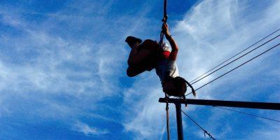 Auf diesem Bild ist ein Mädchen zu sehen, das auf einem Bungee-Trampolin einen Salto schlägt. Im Hintergrund der blaue Himmel.