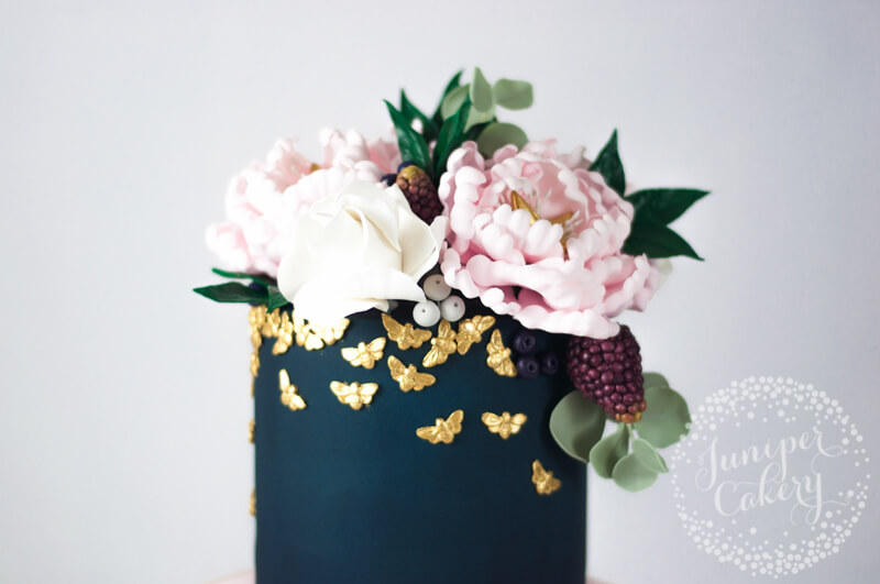 Navy and blush floral peony cake with golden bees by Juniper Cakery