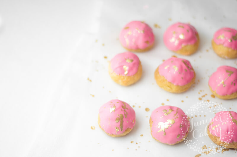 Gold and pink strawberry milkshake cream puffs by Juniper Cakery