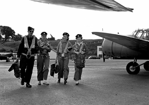 Three photographers getting ready to take off; from left to right: Flight Sergeant A.D. Lang, Aircraftswomen M. Dudlyke, M. Clayborne and Jeanne Farris.