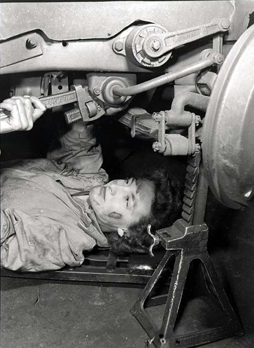 Private Lowry, CWAC, tightening up the springs on the front of her vehicle, Chelsea & Cricklewood Garage , England, July 7th, 1944.