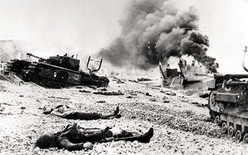 Corpses on the beach next to two Churchill tanks of the 14th Armoured Regiment (Calgary) stuck in pebbles. Behind them, thick smoke coming from LCT 5.