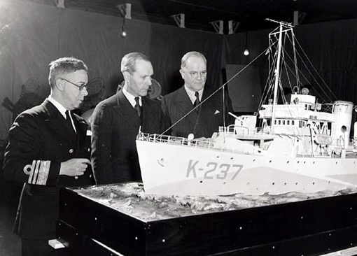 Rear-Admiral P.W. Nelles and Hon. Angus McDonald, Minister of National Defence for Naval Services, taking a look at the model of a corvette at Naval Exhibition, December 1942.