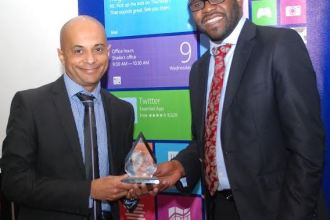 Kunle Awosika From Microsoft Kenya Presents Partner Award to Hasmukh Chudasama From Dimension Data East Africa JUUCHINI