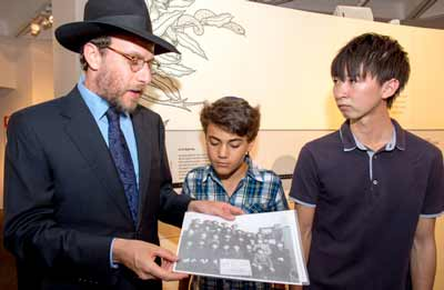 Rabbi Levi Wolff shows Asher Grynberg and Keisuke Sugihara his grandfather's photograph