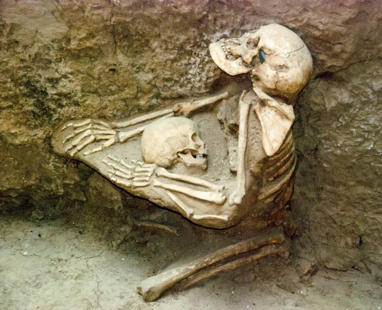Two skeletons, a woman clutching a child to her breast, preserved in a mudflow in Tibet for 4000 years. Photo by Jane Qiu.