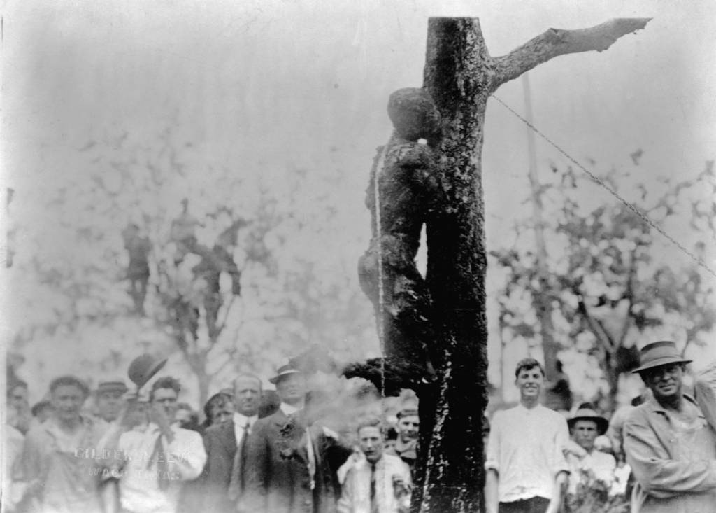 15 May 1916, Waco, Texas, USA --- A crowd of people stands to watch the lynching by burning of Jesse Washington whose charred corpse leans chained to the trunk of a tree. Waco, Texas. --- Image by © CORBIS