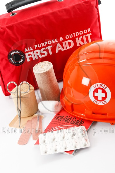 First aid kit with orange safety helmet and first aid supplies.