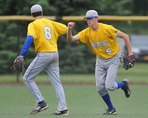Paul Kooney #5, Kellenberg right fielder, right, is congratulated by second baseman Jack Delaney after making a diving catch to end a St. Dominic rally and preserve the Firebirds' 4-3 lead in the bottom of the sixth inning of the CHSAA varsity baseball semifinals at Farmingdale State College on Tuesday, May 24, 2016. Kellenberg went on to win 5-3. (Credit: James Escher)
